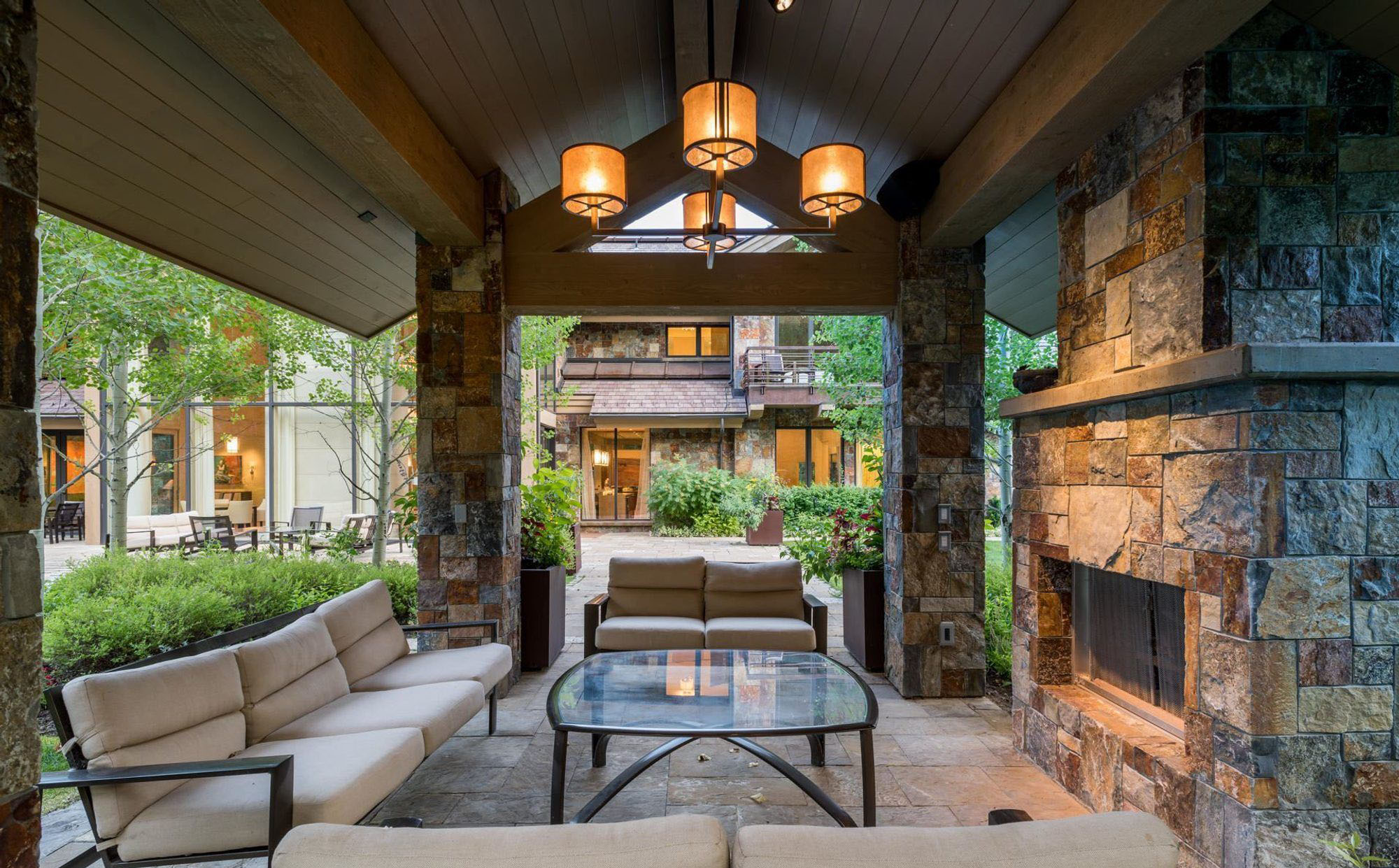Outdoor rustic style wood burning fireplace built with tightly stacked real stone beneath a patio roof. fireplace design ideas.