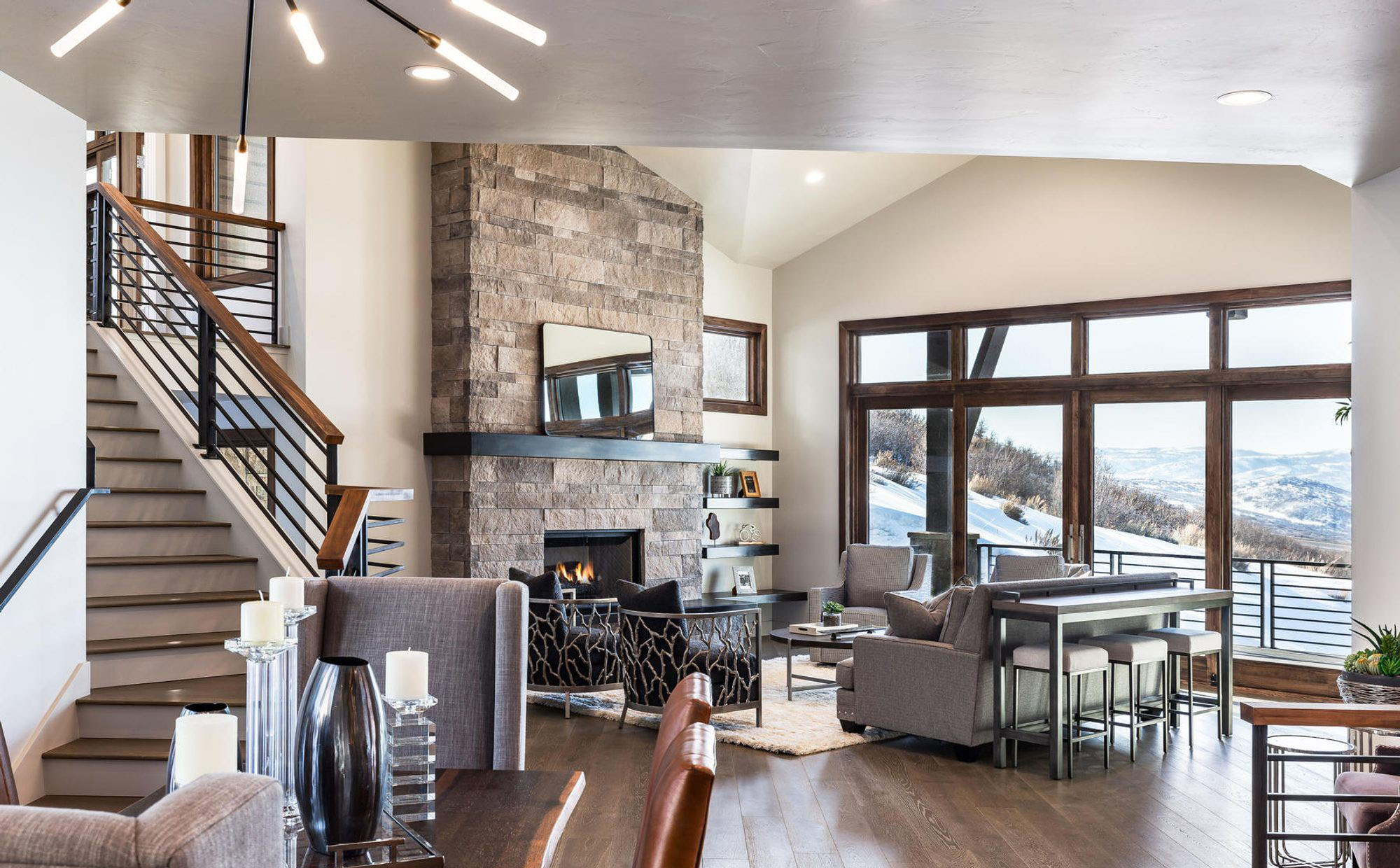 Modern living room fireplace with stacked stone and a black wood mantle.