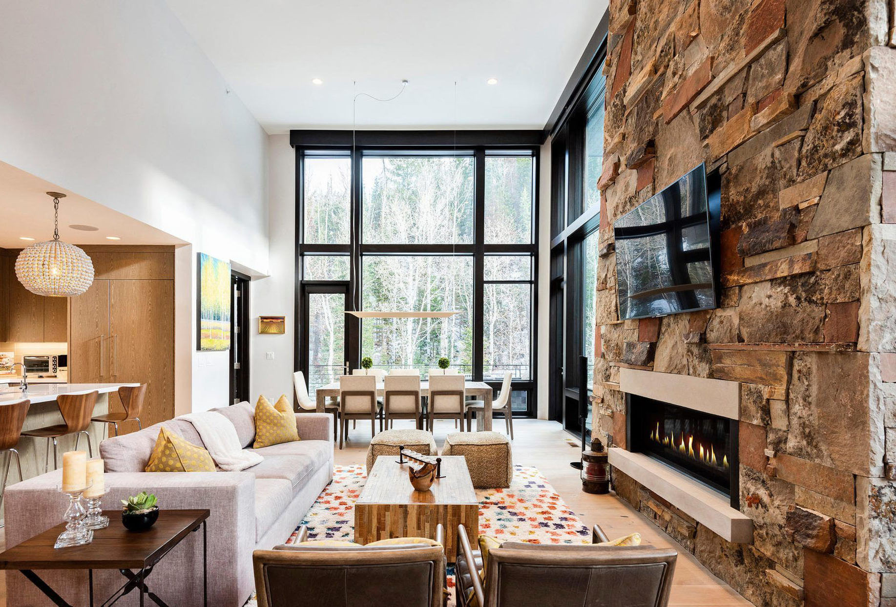 Rustic stacked stone with a warm brown color scheme including a modern style gas fireplace and mounted flat screen TV.