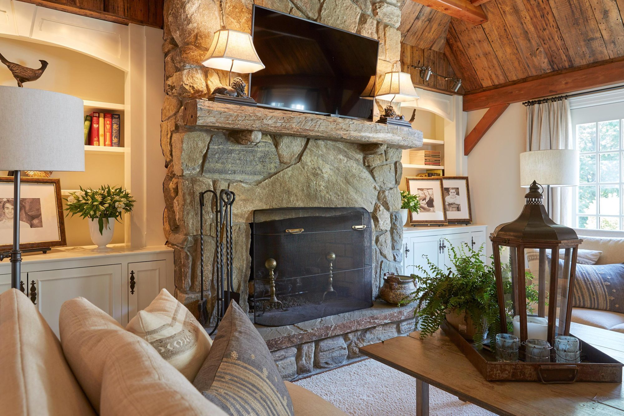Real stone fireplace surround with a rustic style and a raised hearth.