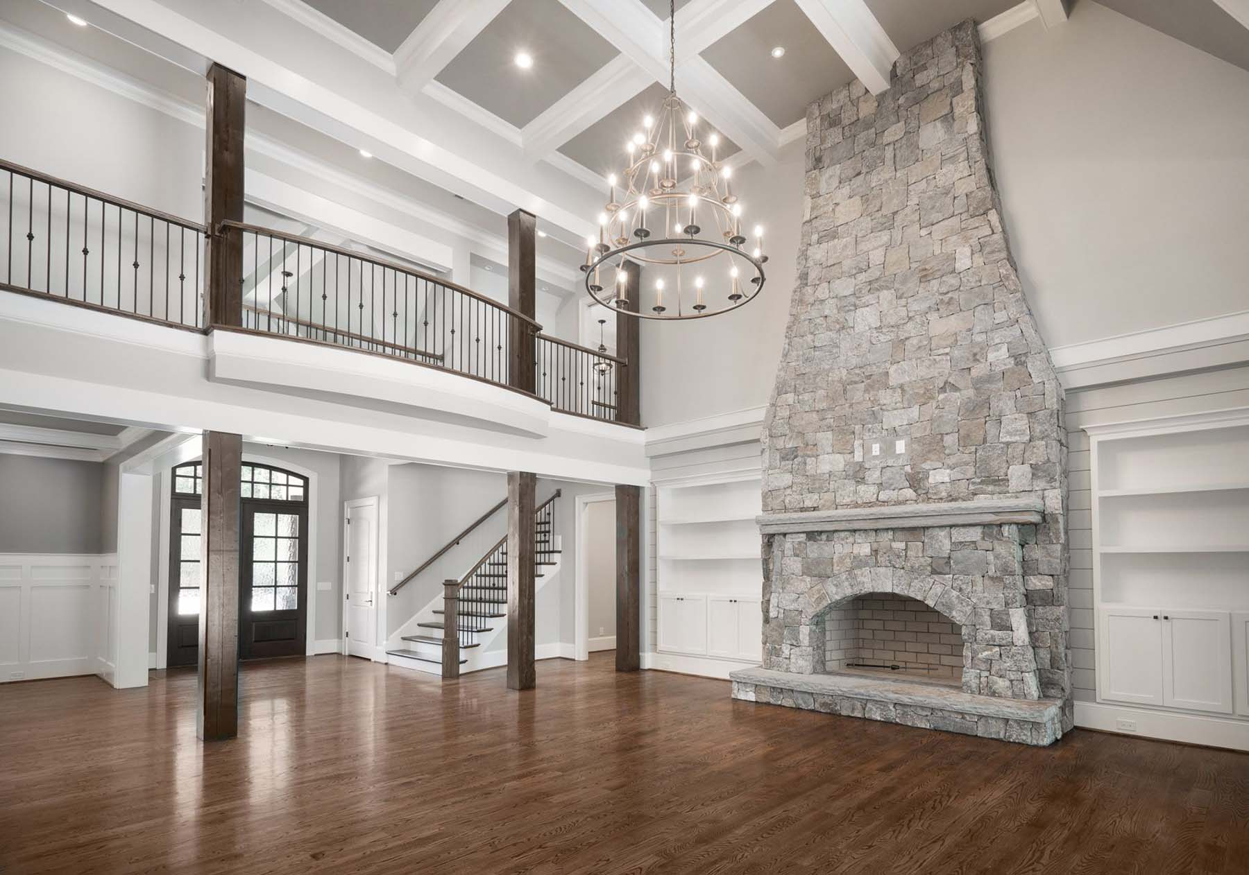 White and gray stacked stone wood burning fireplace with a stone top shelf and raised hearth. fireplace design ideas.