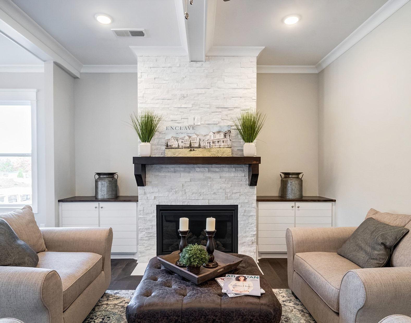 Modern fireplace design using white ledgestone, a black gas firebox and dark wood shelf. fireplace design ideas.