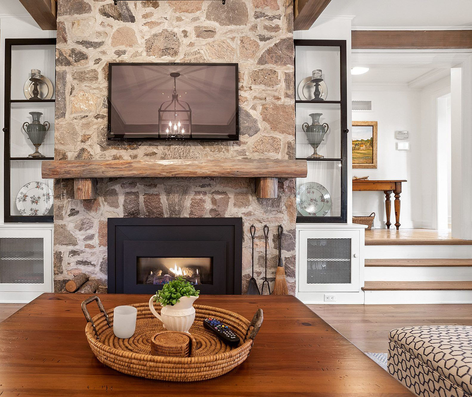 Real stone fireplace surround featuring a warm brown color scheme, gas fire box, a real wood mantle and thick grout lines.