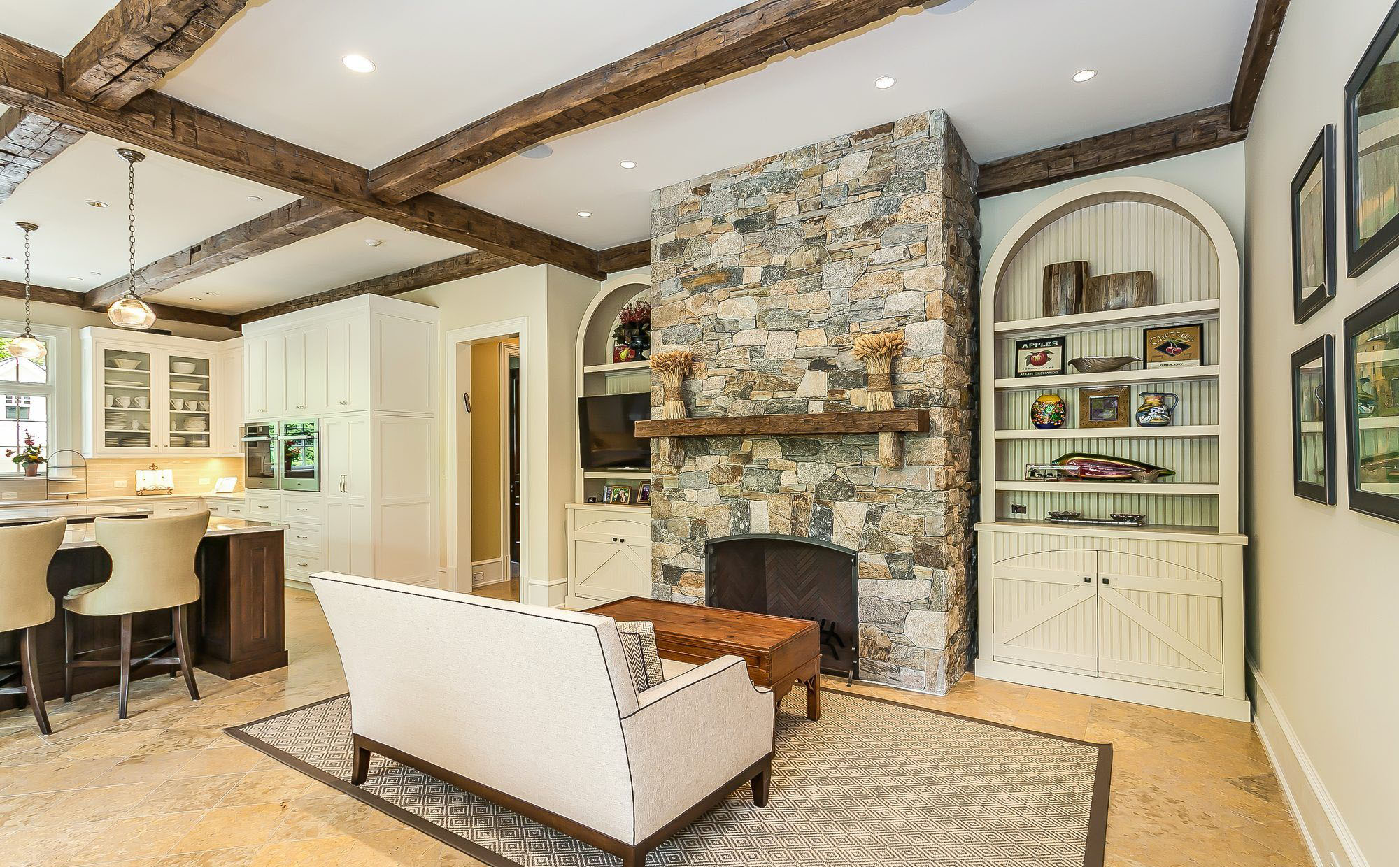 Real stone fireplace surround with a wood top shelf and no hearth. Floor to ceiling stone work.