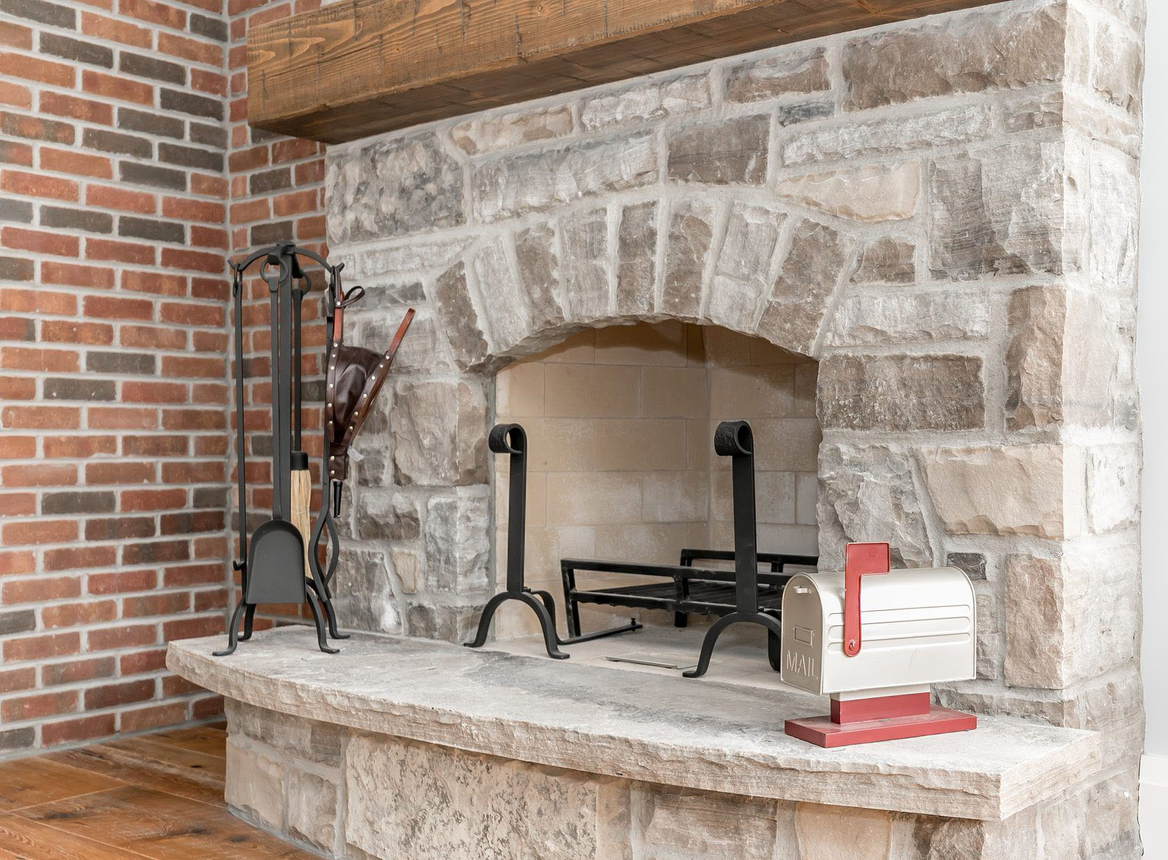 Custom built stone fireplace surround with a raised hearth and wood shelf next to a red brick wall.