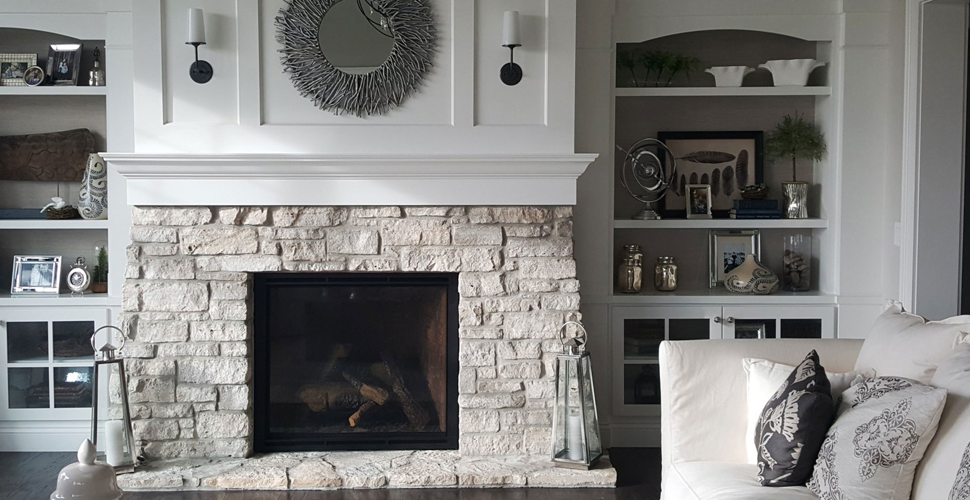 Monochromatic white and cream fireplace surround with real stone, built ins and a wood shelf.