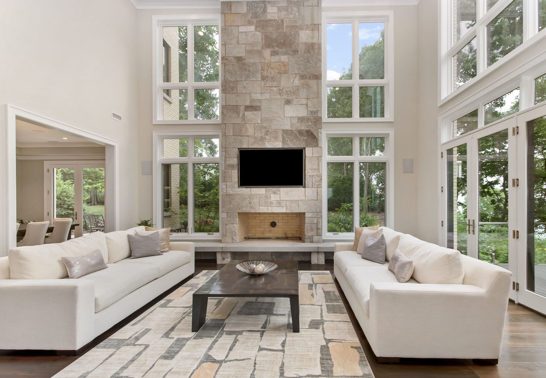 2 story angular stone fireplace surround with tinted grout creates a harmonious color scheme. fireplace design ideas.