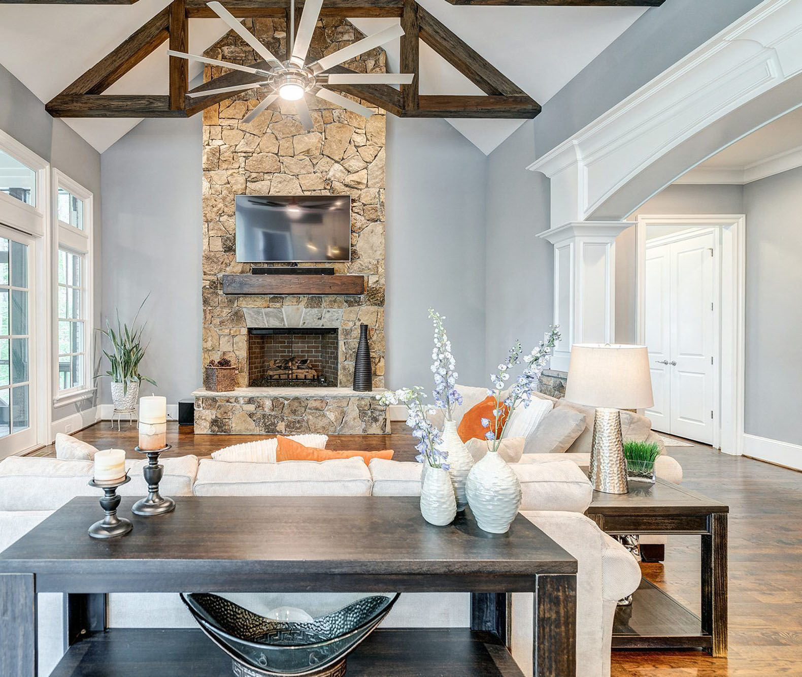 Wood burning fireplace with irregularly shaped real stones, a raised hearth and wood shelf.