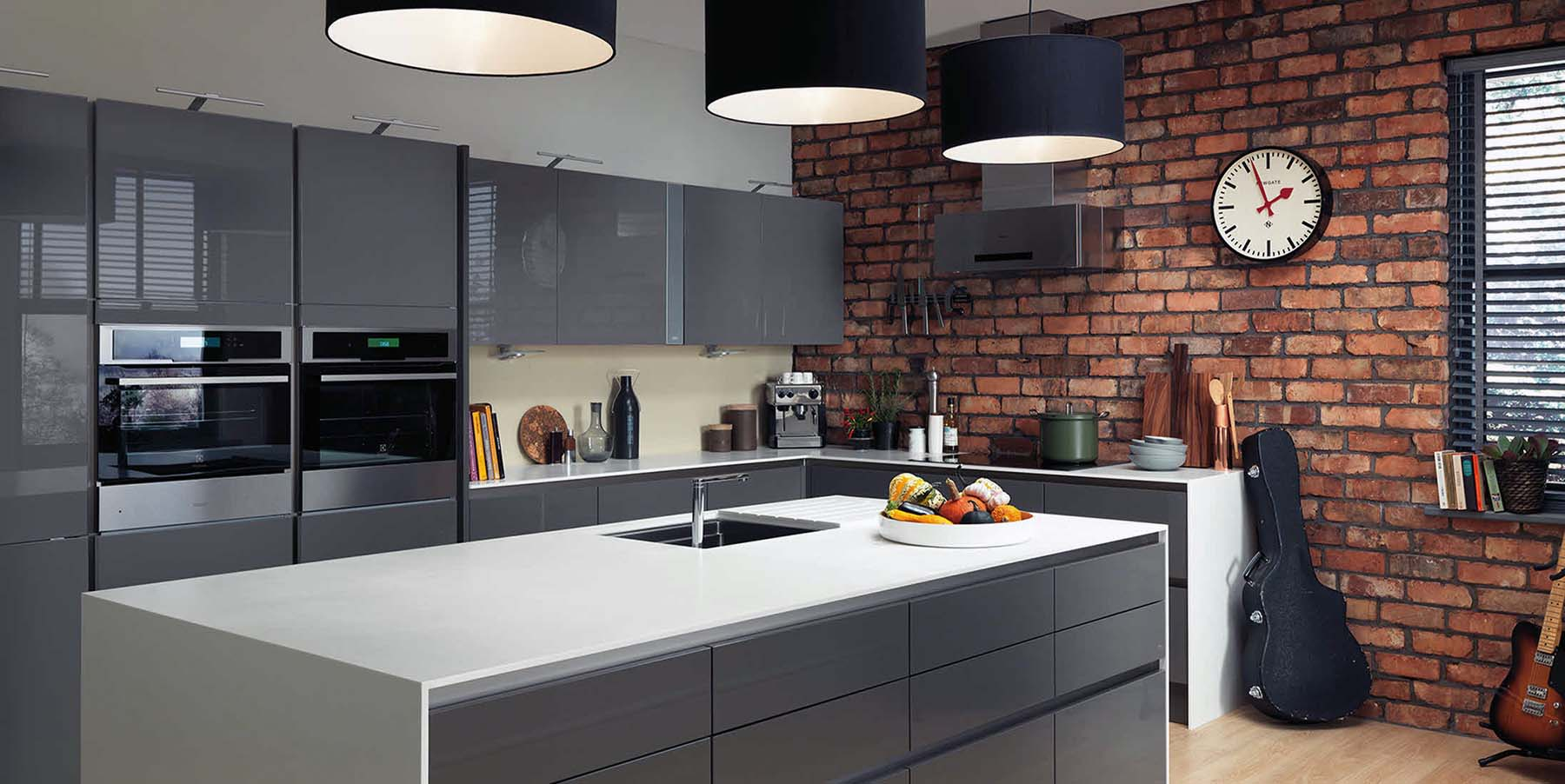 Modern kitchen featuring gray flat faced cabinetry with no hardware, white countertops and a red brick wall.