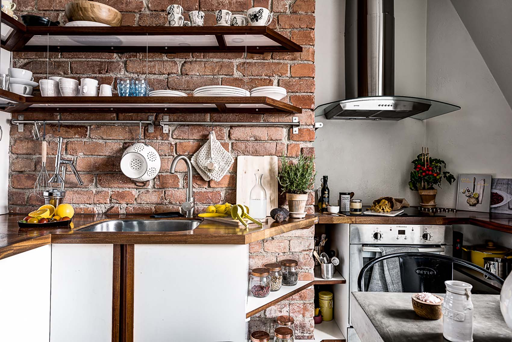 Small rustic kitchen featuring red brick backsplash wall, white cabinets and wood countertops.