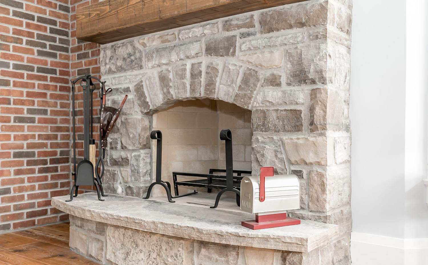 Red brick accent wall next to a stone wood burning fireplace surround with tan brick insert. Thick timber floating mantle.
