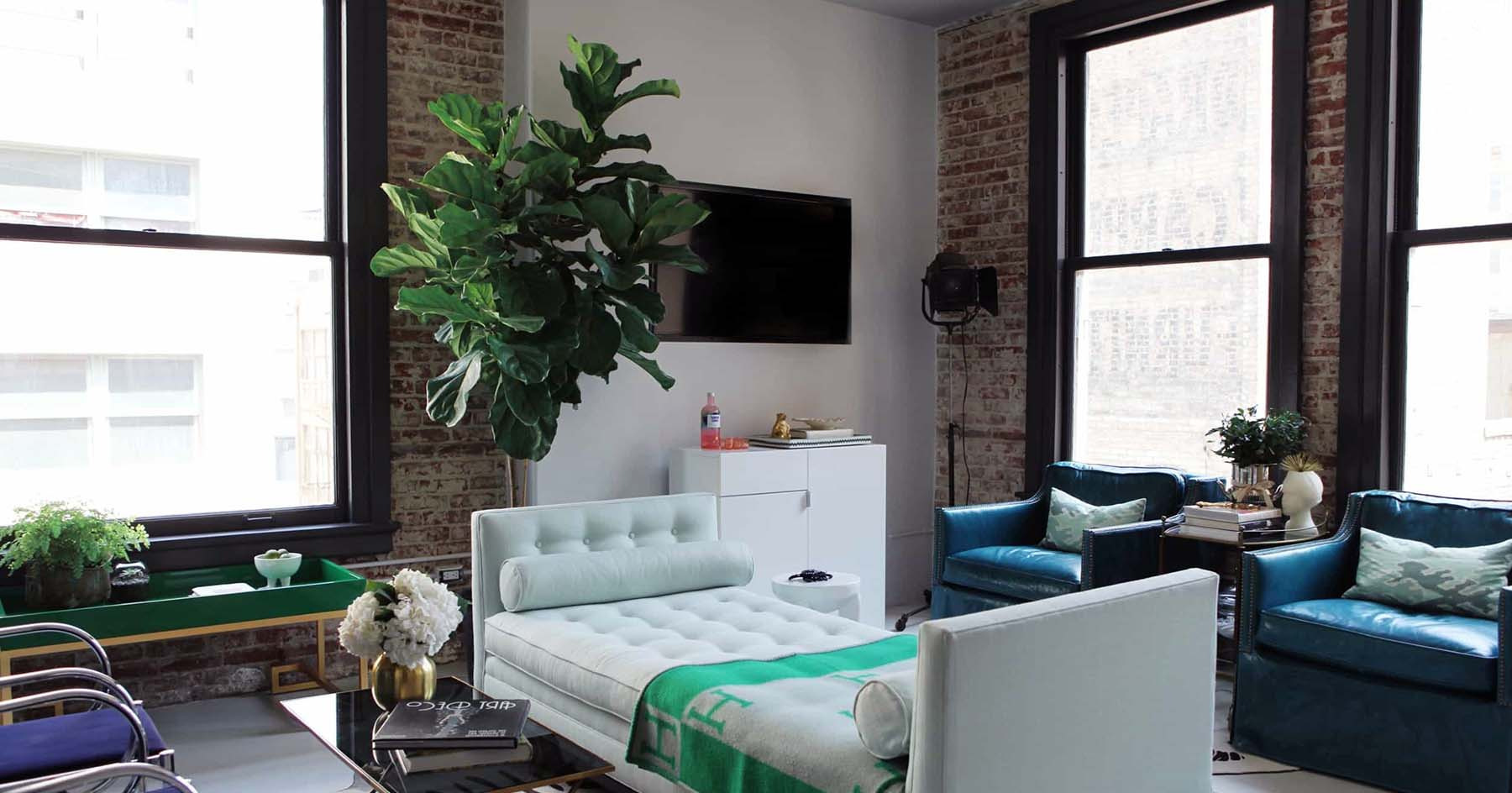 City apartment with red brick walls that are slightly white washed. Black frame windows with drywall and concrete floors give the room a modern feel.