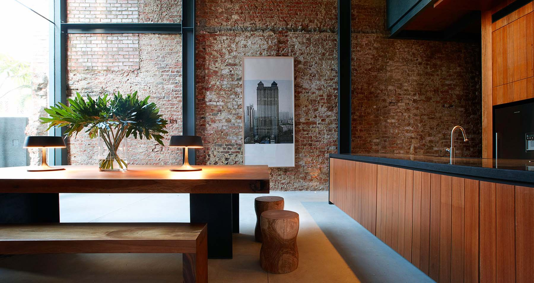 Modern apartment with a red brick feature wall, exposed black steel, wood cabinetry and furniture with concrete floors.