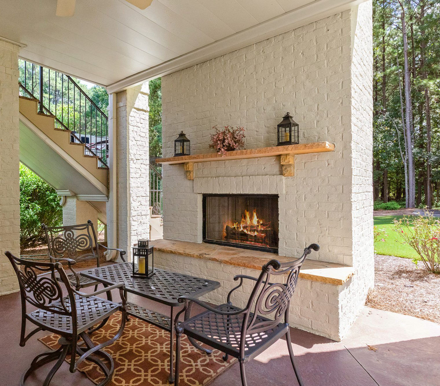 Patio fireplace built with red brick painted white. Wood burning firebox with a tan stone hearth and matching mantle.