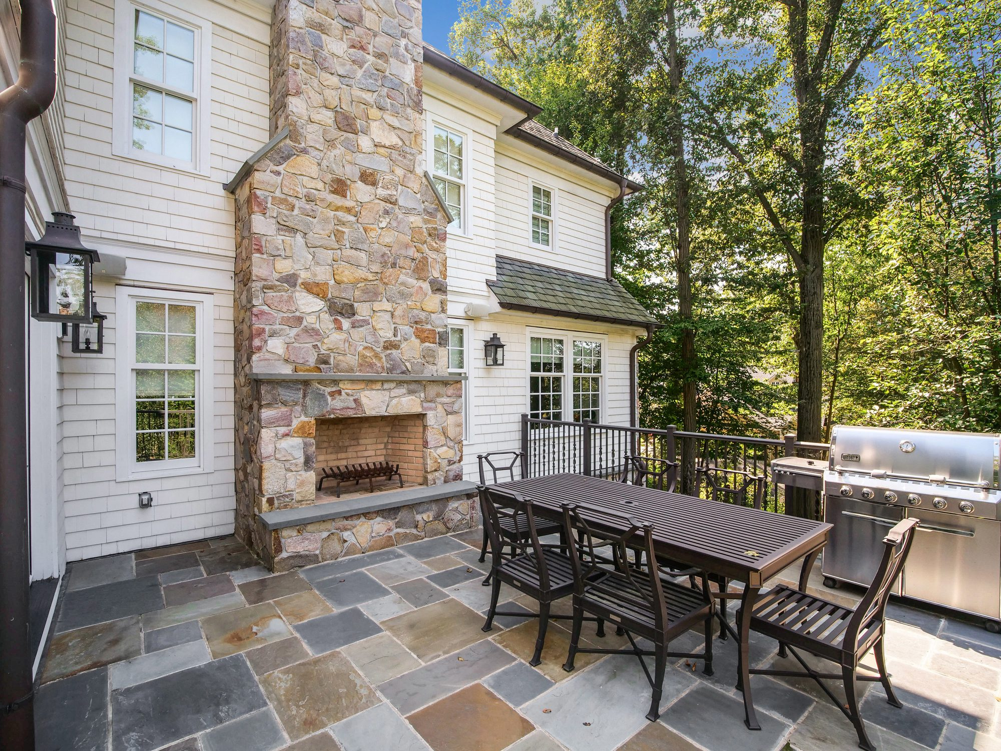 Blue stone patio with a warm colored outdoor fireplace built on the backside of the homes chimney.