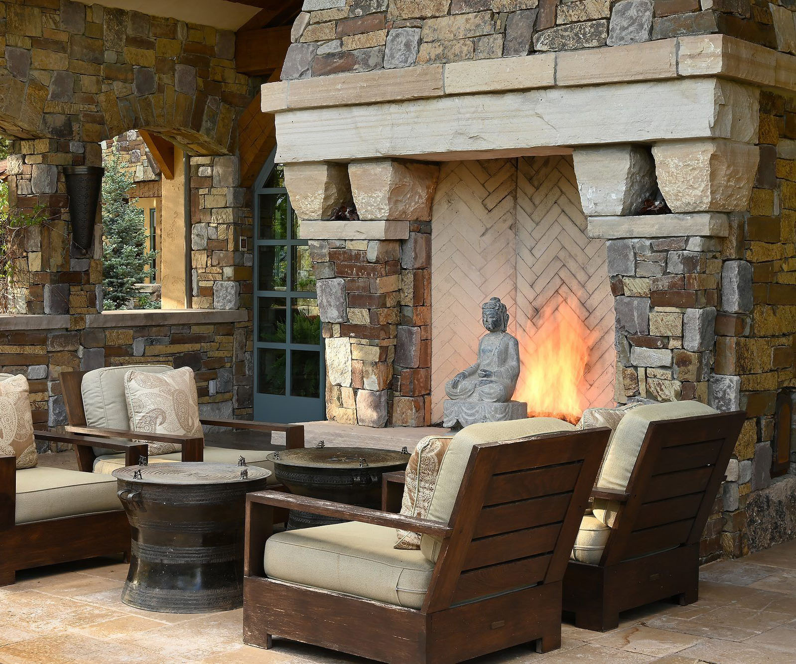 Bohemian inspired outdoor wood burning fireplace design featuring warm colored real stone, a raised stone hearth and thick stone top shelf.