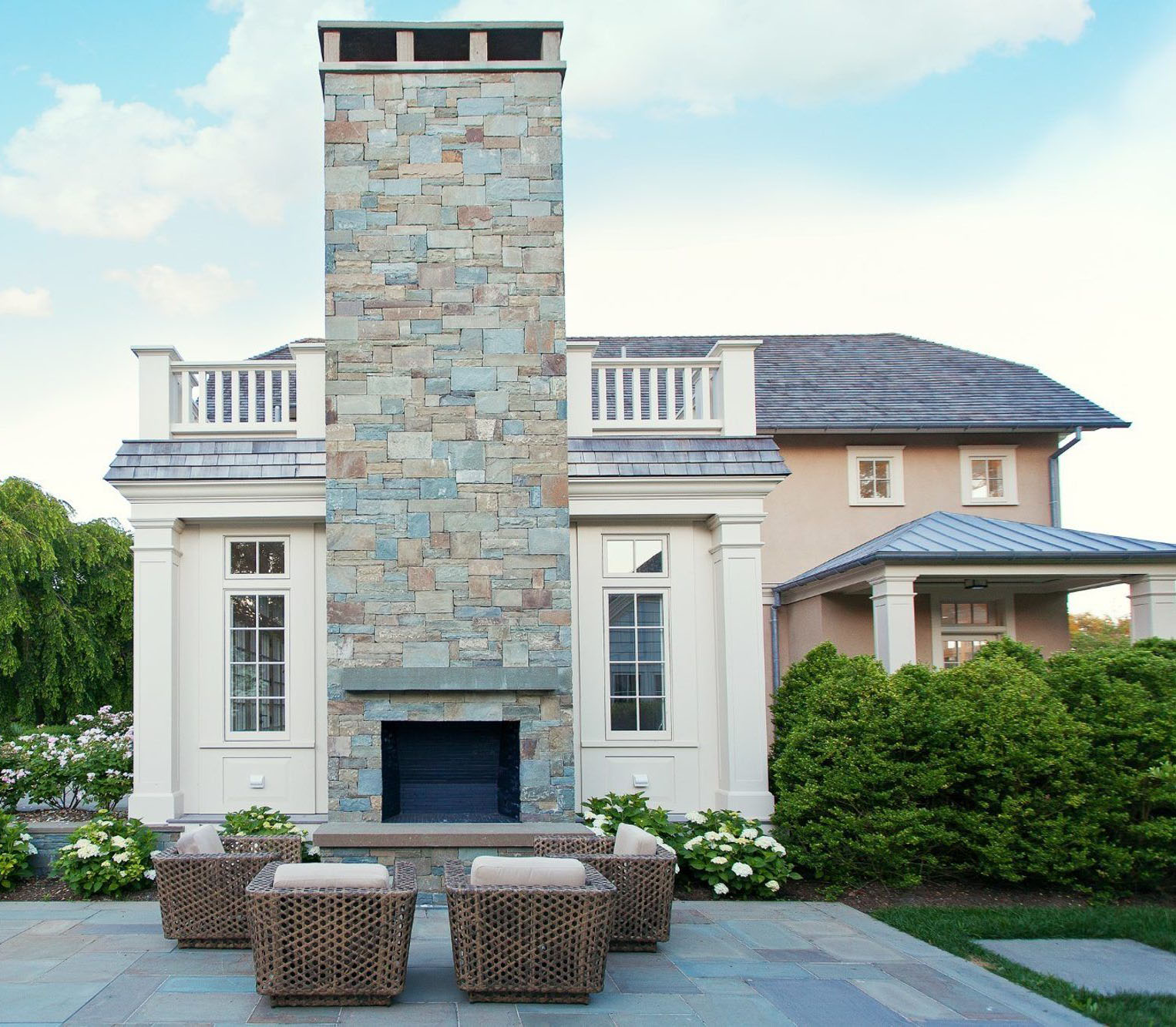 Huge outdoor fireplace with chimney built on a blue stone patio with cast concrete raised hearth and mantle.