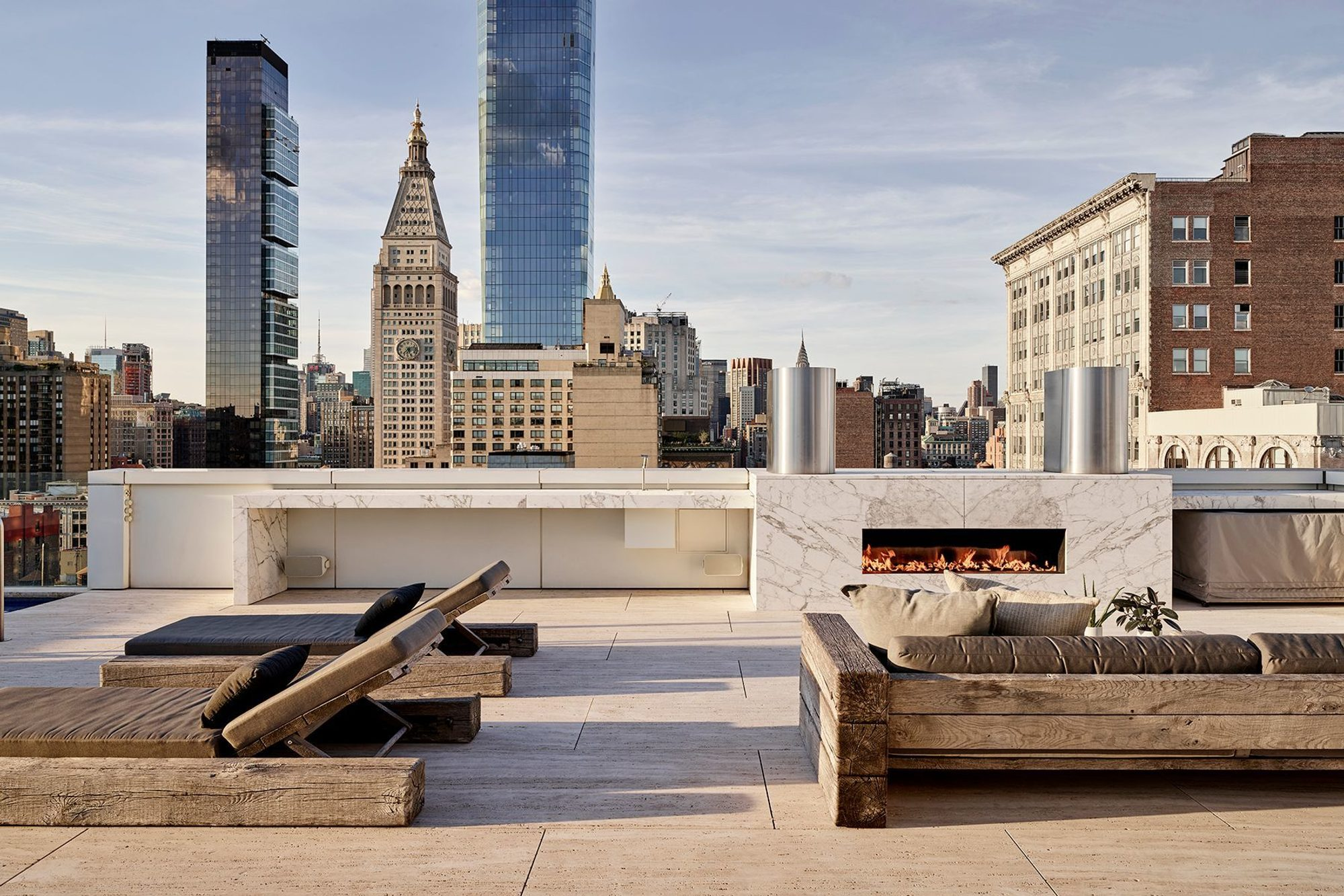 Rooftop city patio fireplace finished with a marble slab.