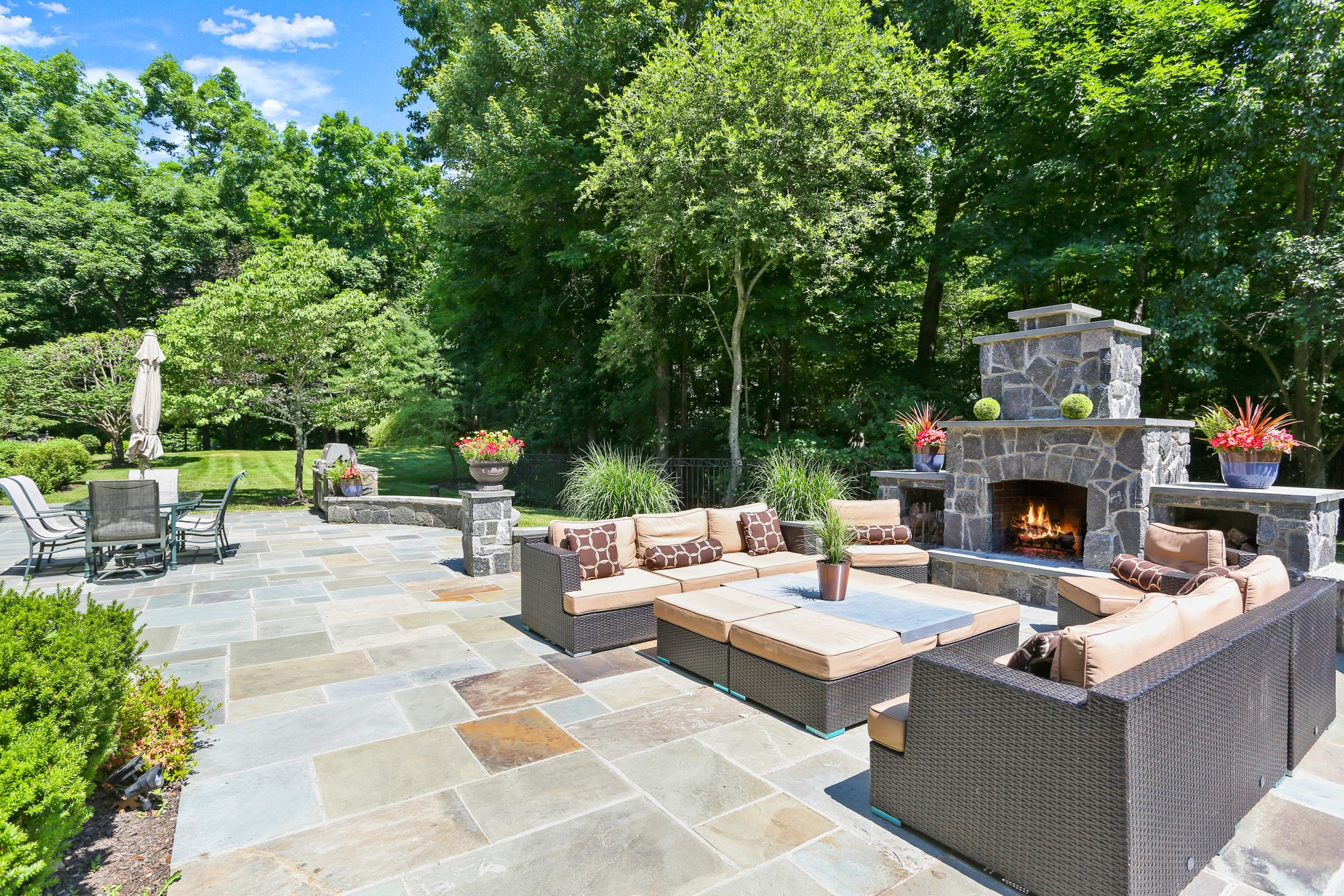 Wood burning patio fireplace built out of stone with a raised limestone hearth and matching mantle with side shelves for wood storage.