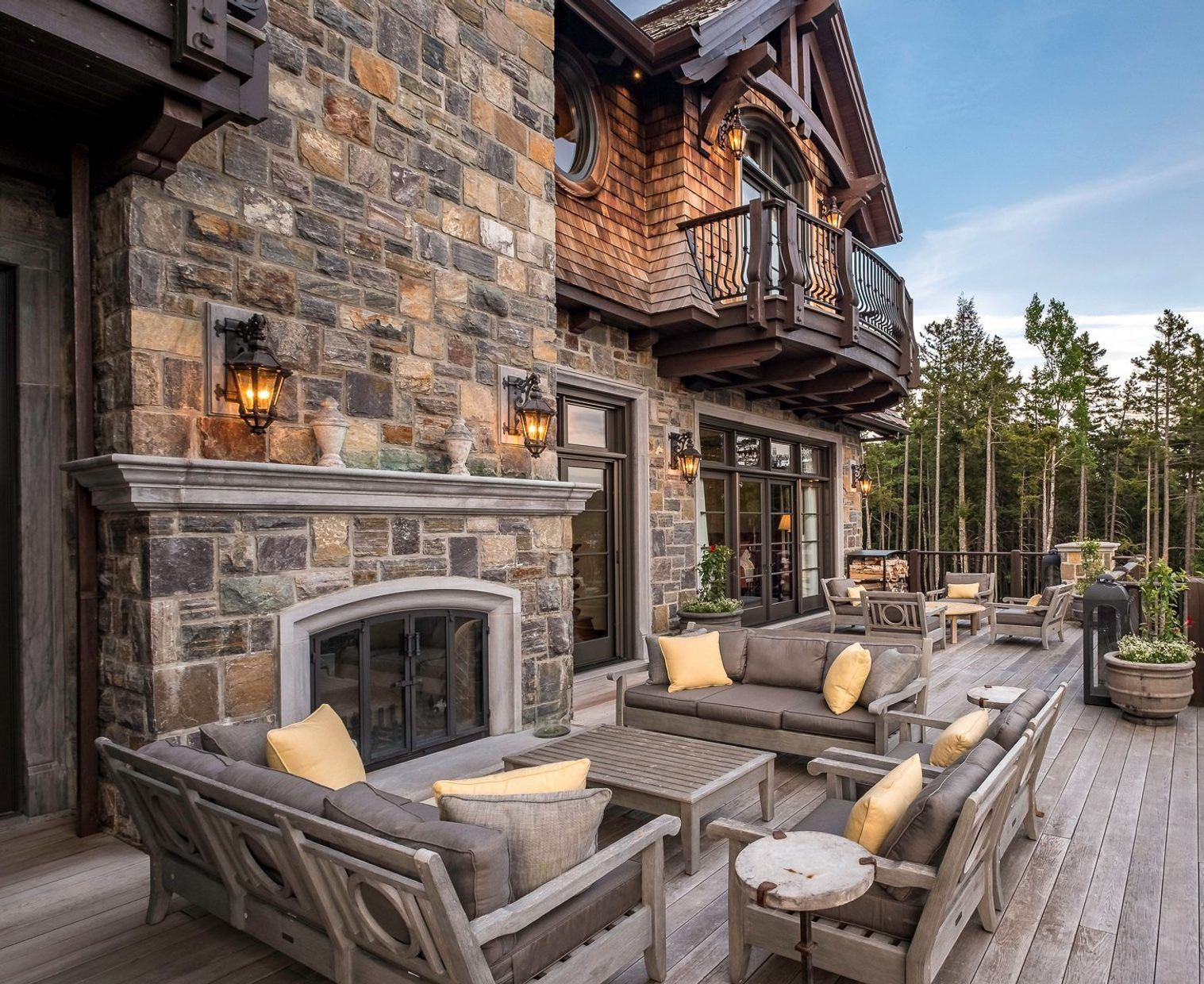 Outdoor country style fireplace built on a deck out of real stone and cast cement trim. fireplace design ideas.