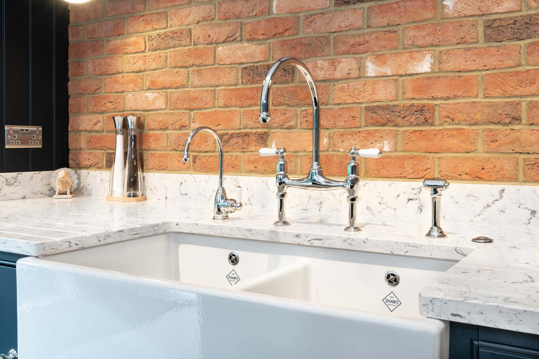 White farmhouse double sink with marble countertops, chrome faucets and a red brick wall.