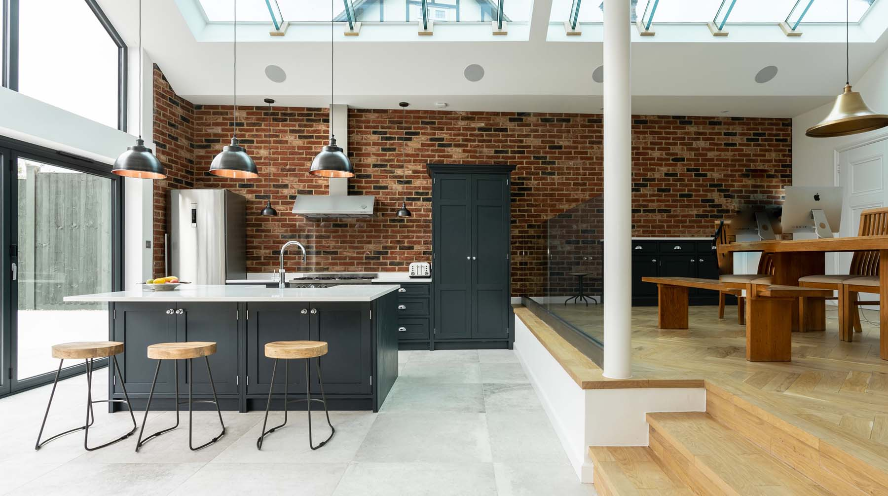 Red brick wall in an open floor plan modern home with vaulted ceilings and a glass roof.