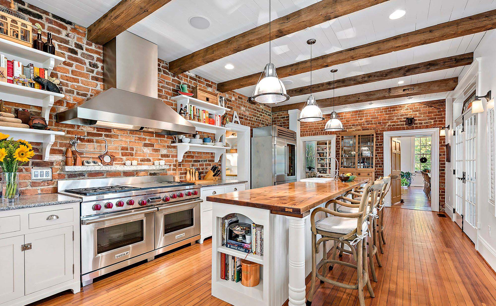 Country style kitchen with red brick walls, white cabinets and lots of real wood.
