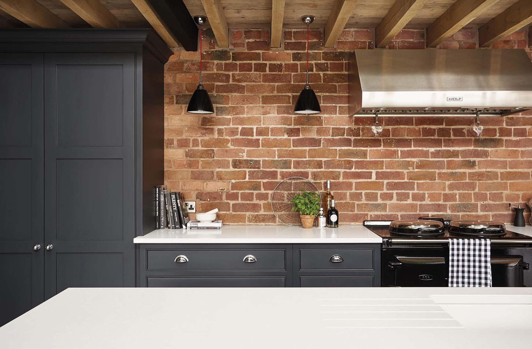 Dark gray kitchen cabinets with white stone countertops and a red brick wall. Antique style black stove with a stainless steel hood.