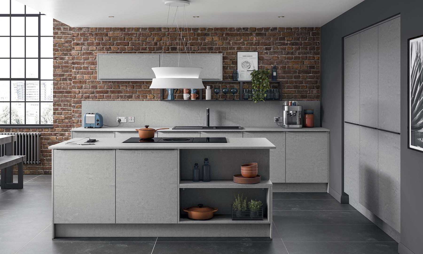 Gray kitchen color scheme with a red brick wall. Modern designed cabinets with flat faces and no hardware.