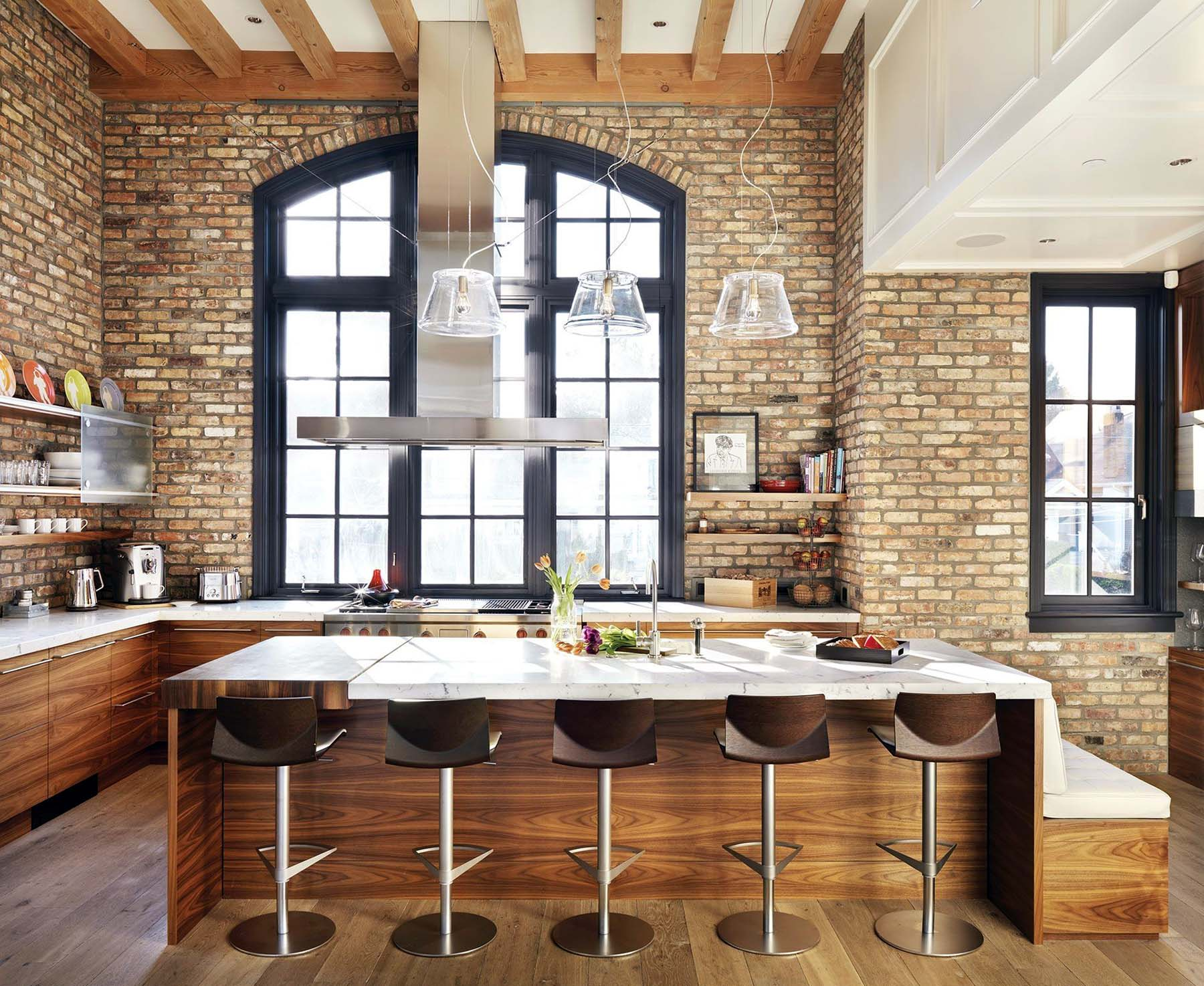 Beautiful contemporary kitchen design with cathedral ceilings, exposed wood beams, real wood flat faced cabinets, and red brick walls.