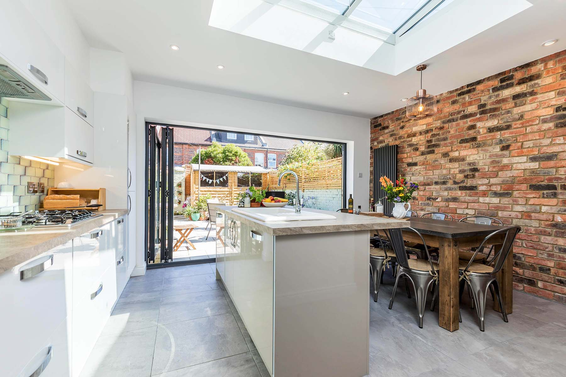 Red brick accent wall in an open concept kitchen with folding patio doors.