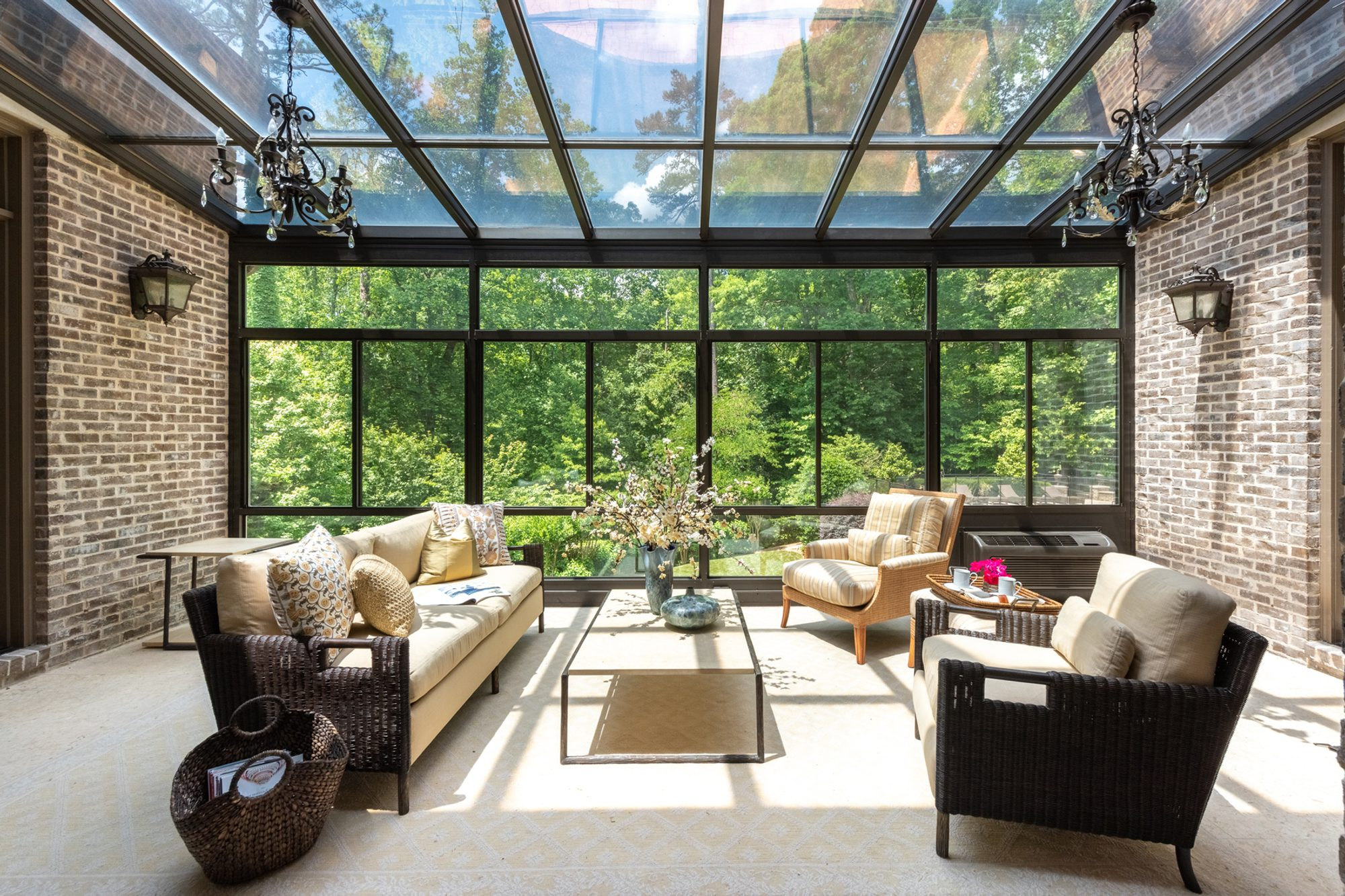 All glass enclosed sunroom with red brick walls.