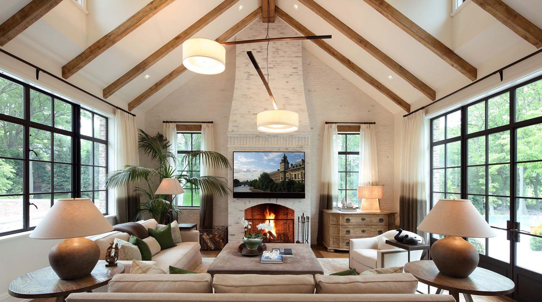 Red brick wall and fireplace surround painted white in a sunroom with vaulted ceilings.