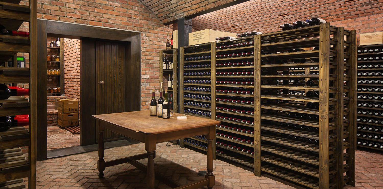Custom built wine cellar with red brick walls, floor and ceiling. Custom built wood racks.