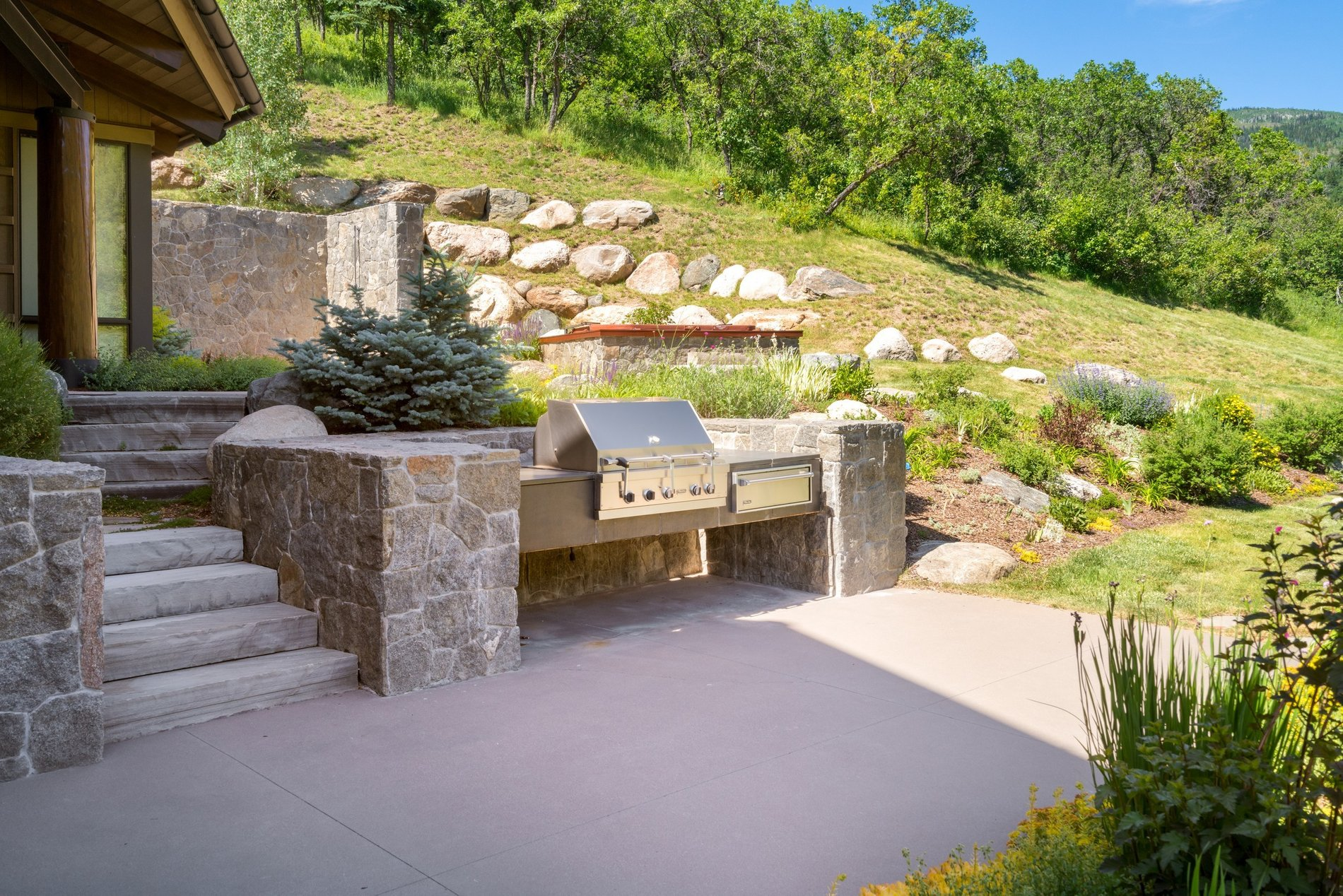 Outdoor grill area made from real stone with a stainless steel grill. Stone steps leading to a concrete patio.