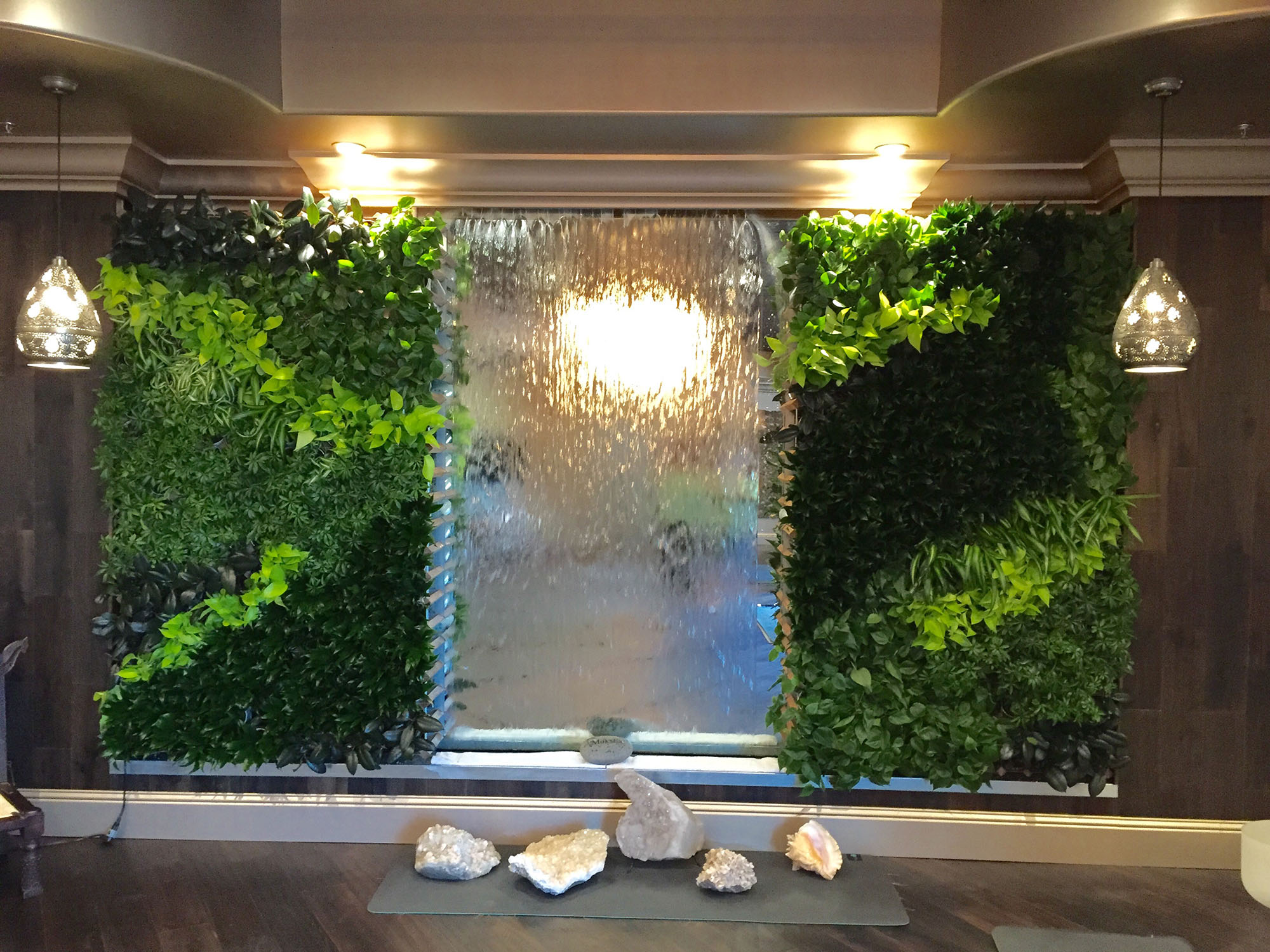 Plant wall surrounding an indoor water feature.