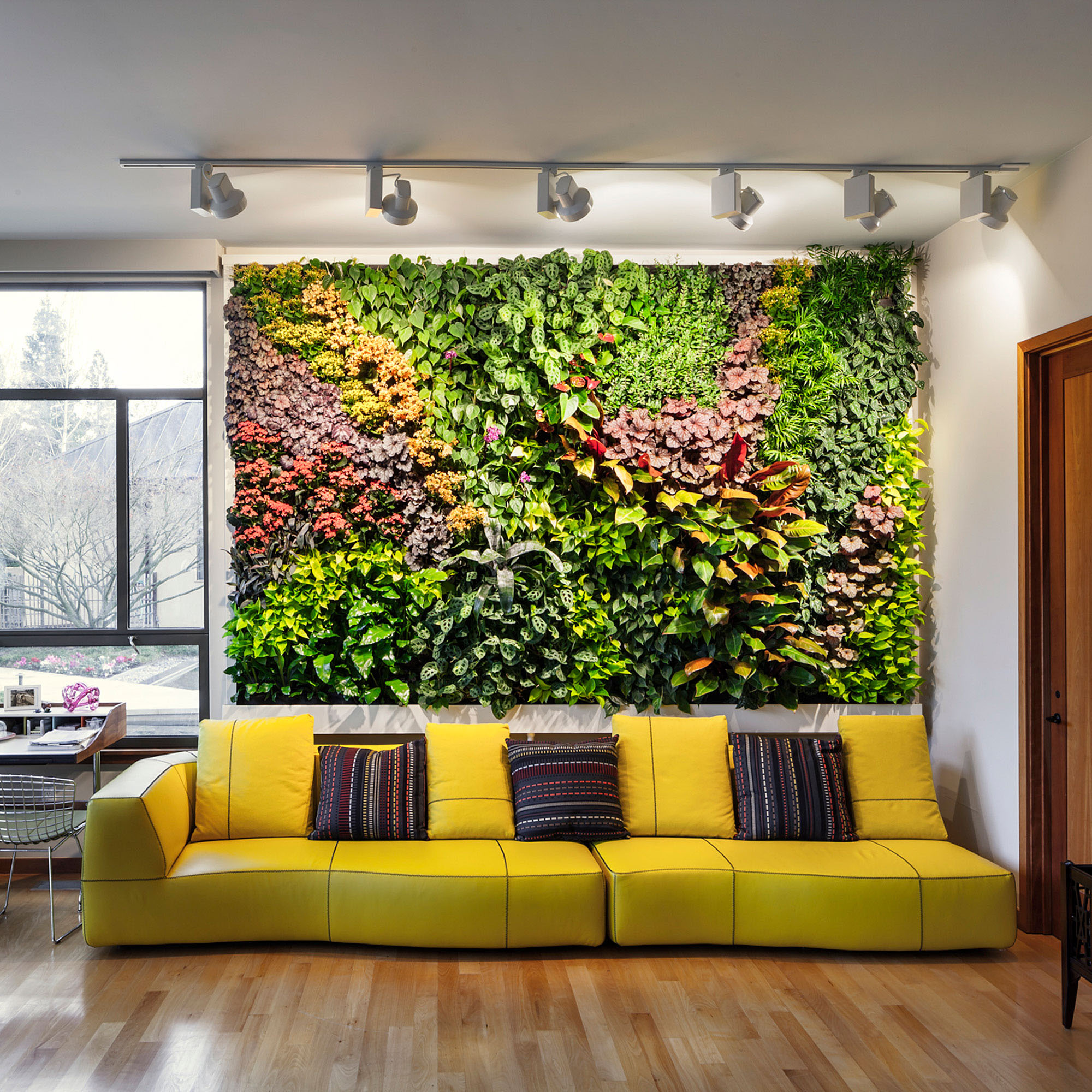Colorful living green wall art above a bright yellow sofa with lots of lighting.