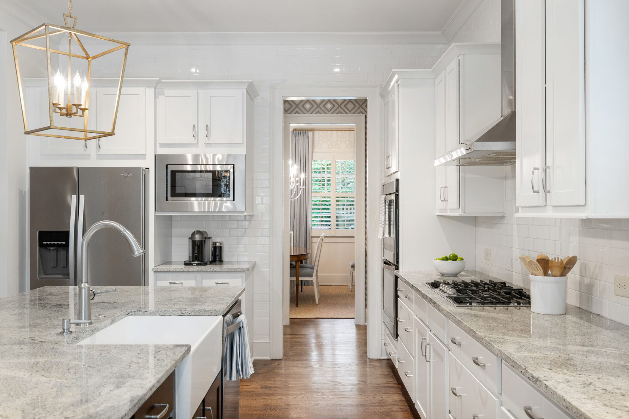 White farm house sink in a center island with black cabinets and gray granite countertops.