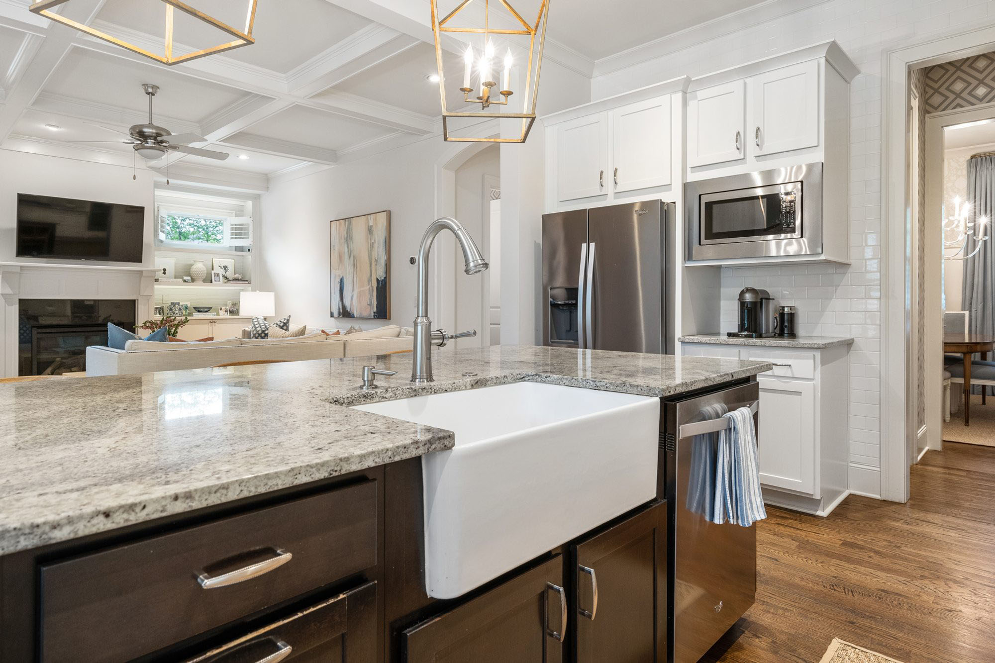 Closeup view of a white farmhouse island sink with black cabinets and gray granite countertops.