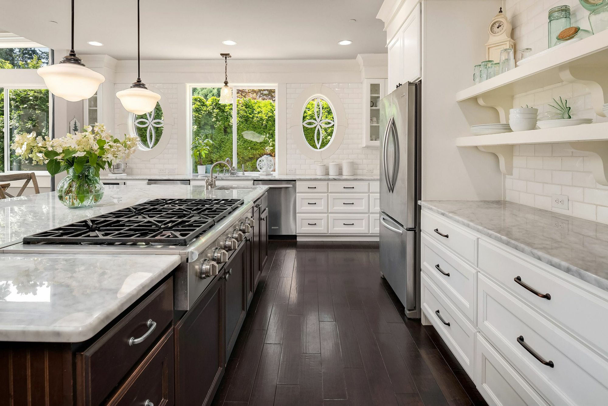 Beautiful luxury kitchen design with white cabinetry, darkly stained island, stainless appliances and marble.