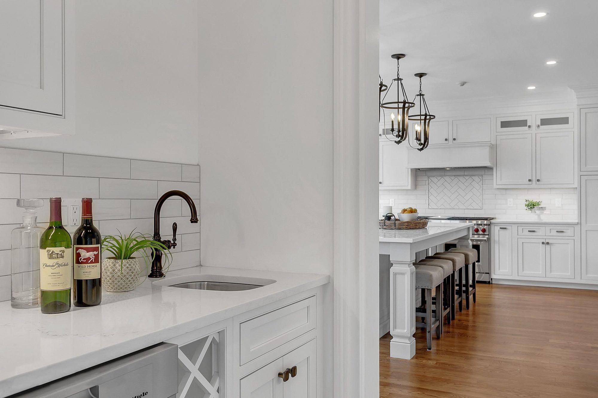 Prep kitchen with small sink, white countertops and white subway tile backsplash.