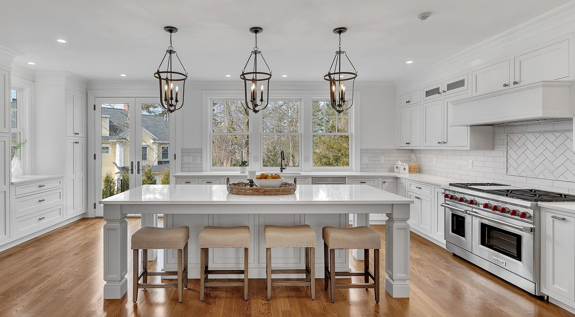 Beautiful white kitchen with stained hardwood floors.