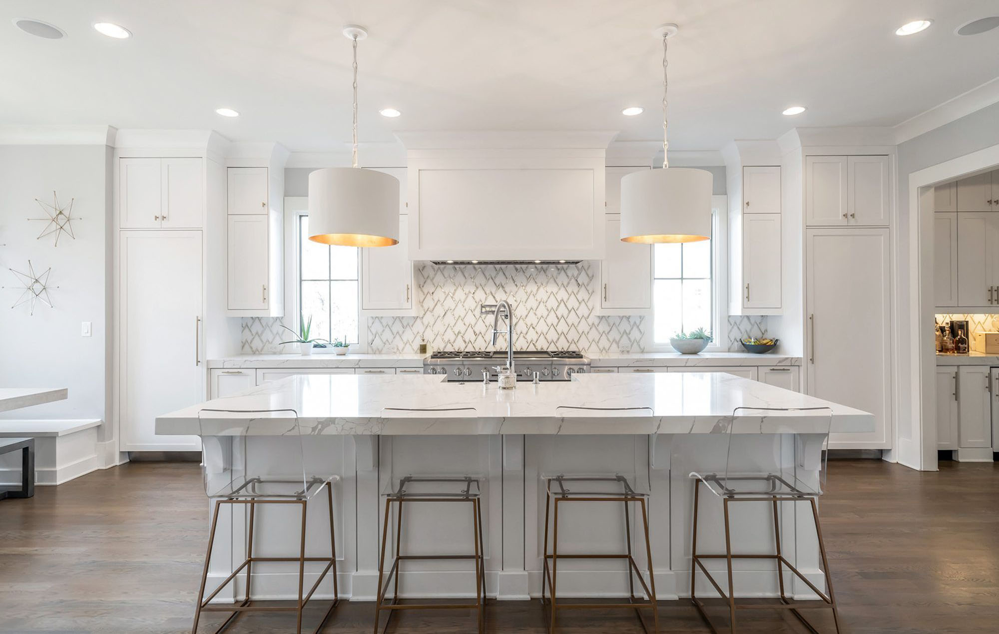 White shaker style kitchen cabinets with marble quartz countertops, brown hardwood floors and glass stools.