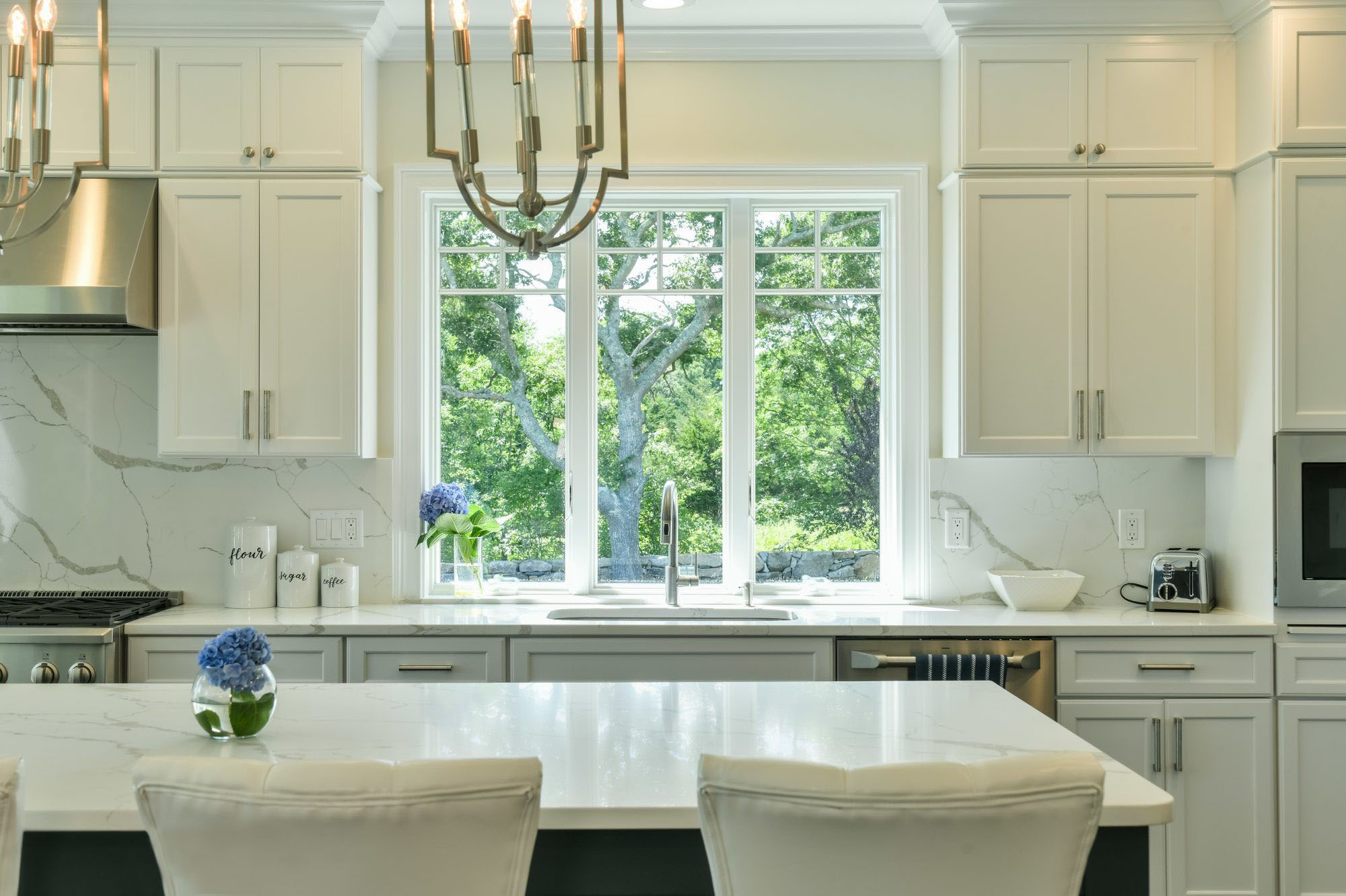 Traditional white kitchen using warm cream and marble with stainless steel appliances.