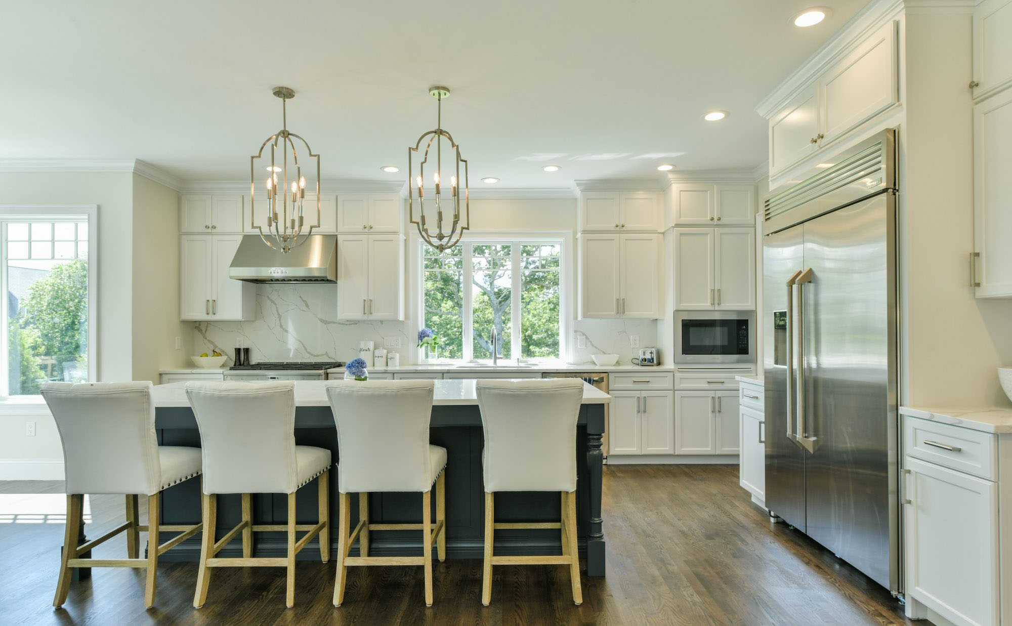 Cream kitchen cabinets with marble countertops and matching solid slab backsplash. Dark gray island with plush seating.