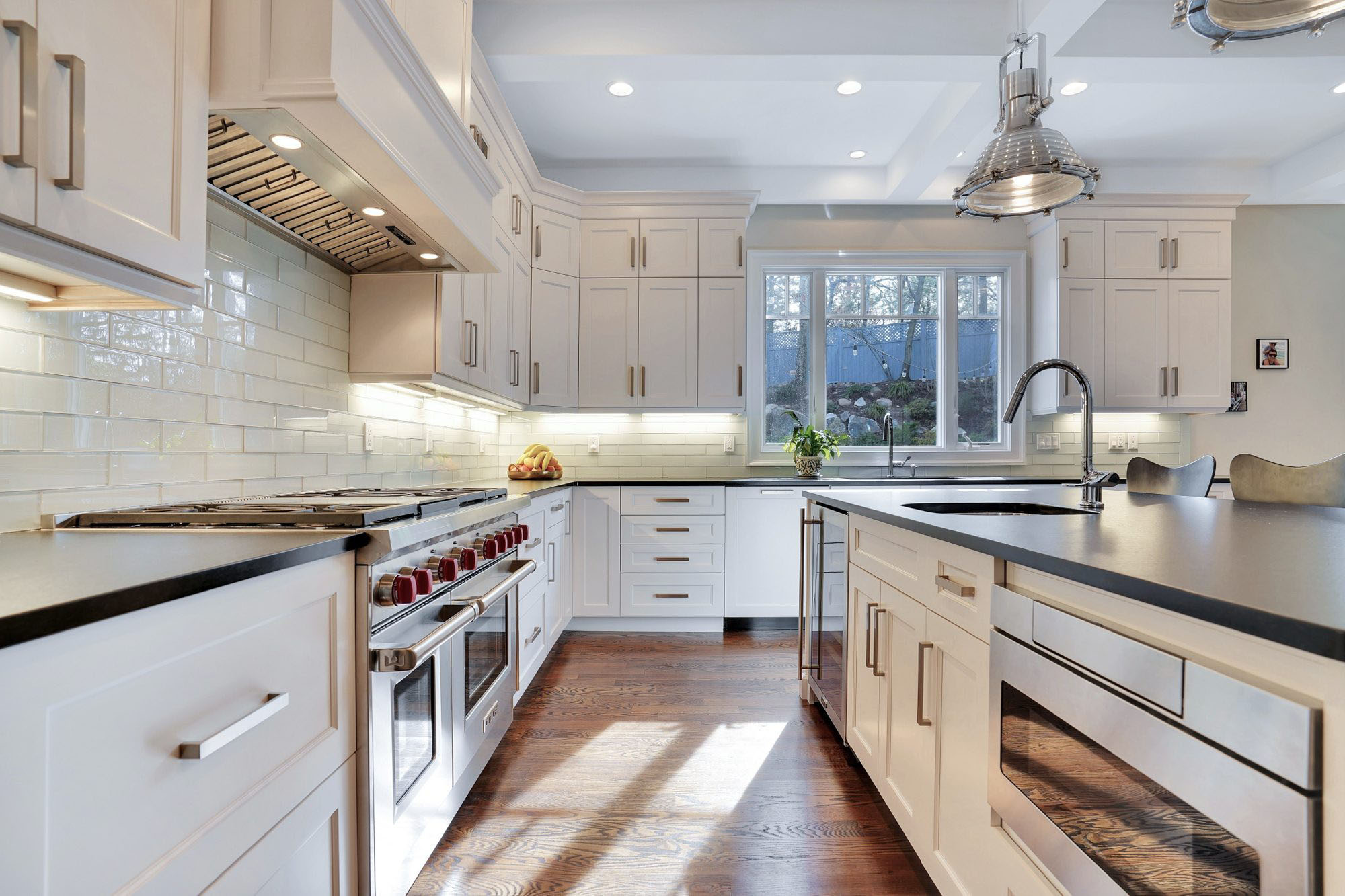 White shaker style kitchen cabinets with white subway tile backsplash and gray countertops.
