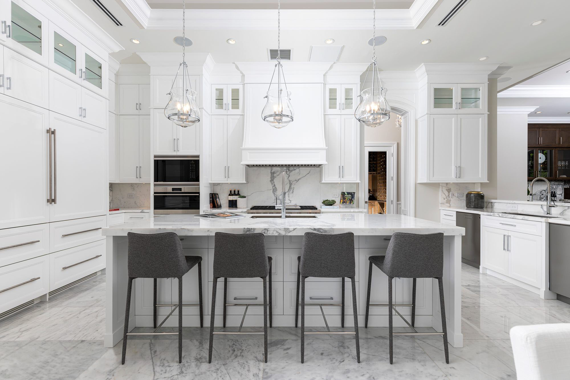 Beautiful luxury kitchen with tons of white, gray and marble.