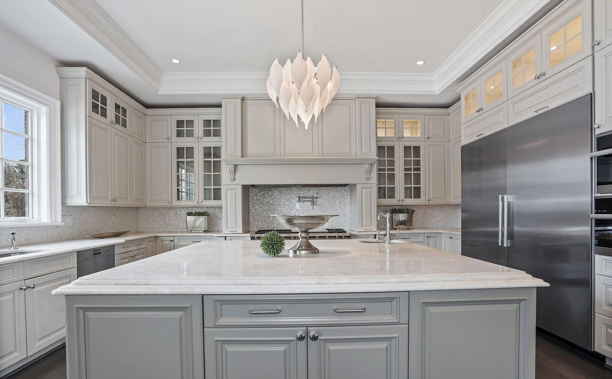 Cream kitchen cabinets with light gray island and marble countertops. Sparkly tile backsplash.