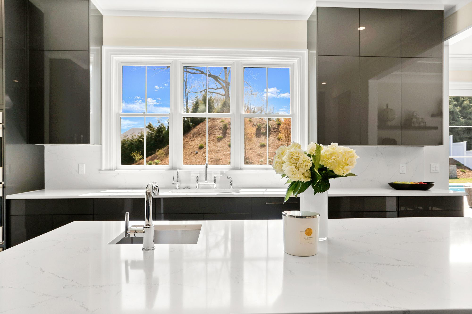 Transitional kitchen design with flat faced black cabinets, white quartz countertops and traditional trim.