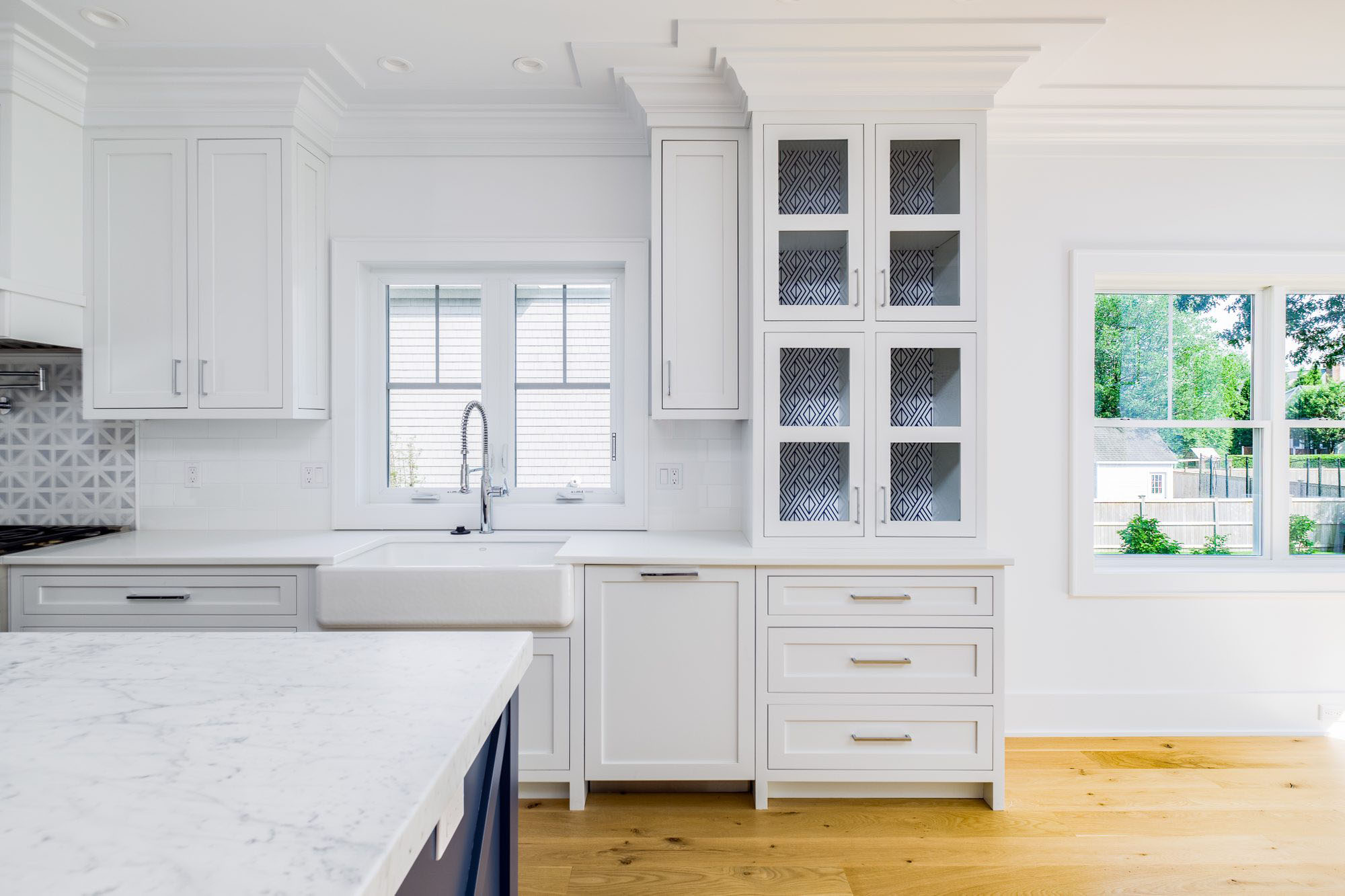 White kitchen with blue island and other blue accents. Shaker style cabinets.